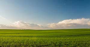 Wide photo of green plains with clouds and the sky in the backdrop.